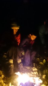 Image of two girls sat in front of camp fire in snow in the dark