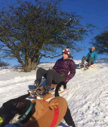 Image of woman and man sledging down a steep hill with running dog in foreground