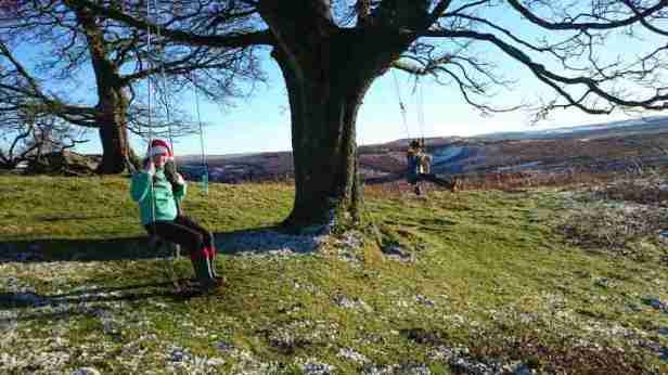 Image of woman in jeans, wellies and santa hat with girl in blue coat both on rope swings on a tree on open moorland