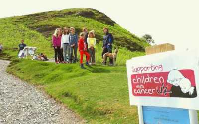 Image 2 of woman and girls with dog on steep hill with cancer charity sign in foerground and cake stall behind