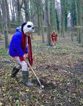 Image of girl in blue coat digging hole in woodland with girl in red coat digging hole in background