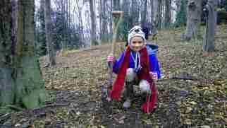 Image of girl in blue coat in woodland holding sapling and spade
