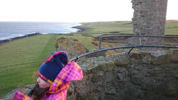 Image of girl in pink and orange coat and blue hat looking out over castle battlements with panorama along coast and sea behind
