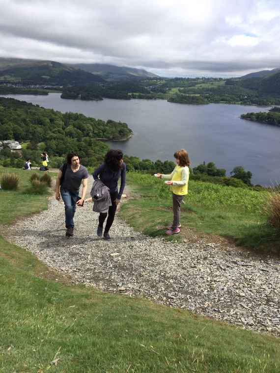 Image of girl in yellow Brownie jumper offering cakes to walkers on steep hill with stunning lake view below