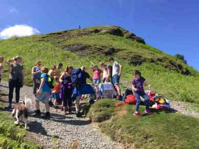 Image of group of adults, children and dogs buying cakes from hillside charity stall with steep hill behind